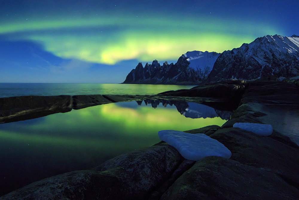 The Northern Lights (aurora borealis) and stars reflected in the icy sea, Tungeneset, Senja, Troms county, Arctic, Norway, Scandinavia, Europe