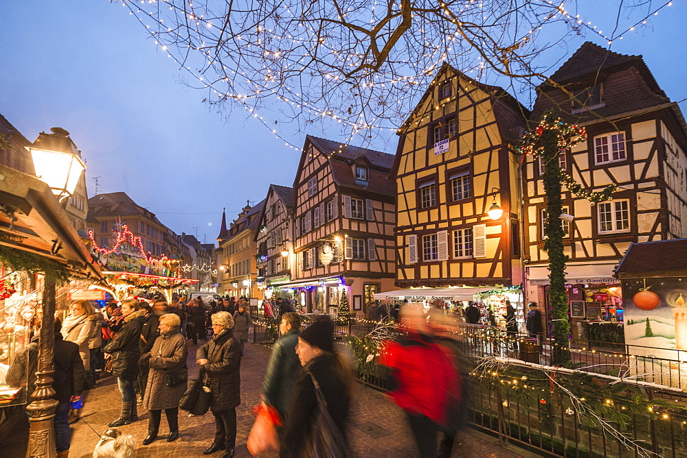 Tourists shopping at the Christmas Markets in the old medieval town of Colmar, Haut-Rhin department, Alsace, France, Europe