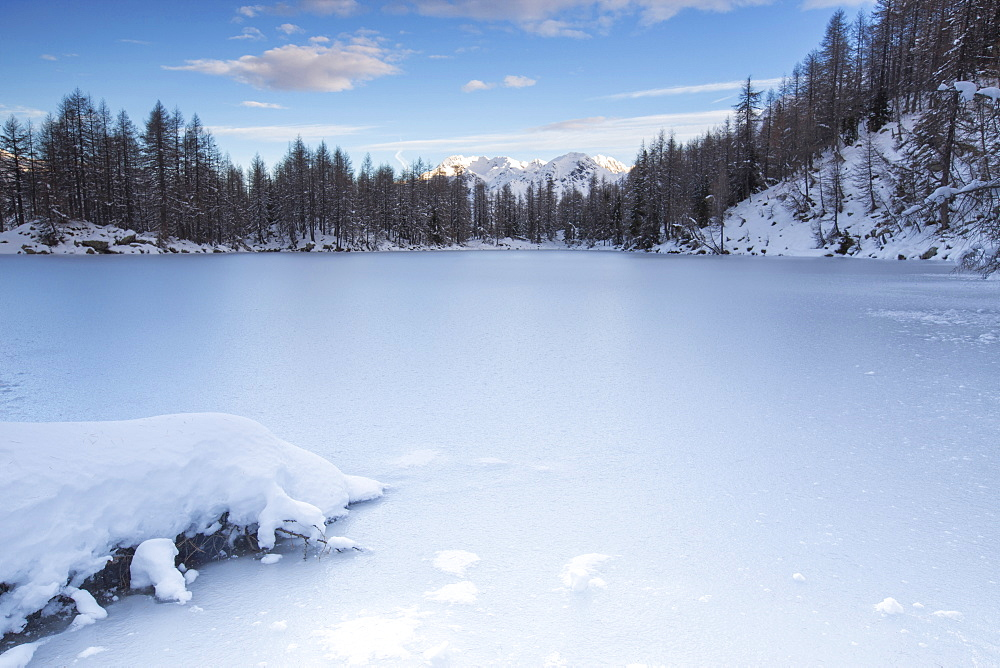 View of the frozen Lago Azzurro surrounded by snow at dawn, Spluga Valley, Province of Sondrio, Valtellina, Lombardy, Italy, Europe