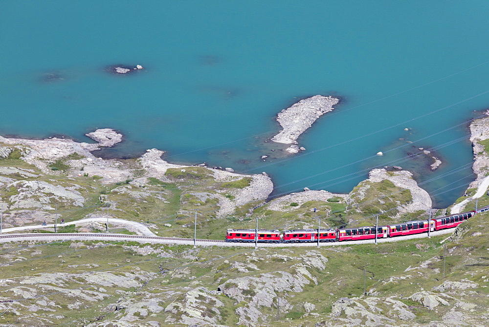 The Bernina Express train passes on the shores of Lago Bianco, Bernina Pass, Canton of Graubunden, Engadine, Switzerland, Europe