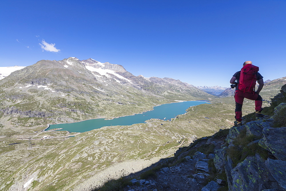 Hiker admires the blue alpine lake from Pizzo Campaccio, Bernina Pass, Canton of Graubunden, Engadine, Swiss Alps, Switzerland, Europe