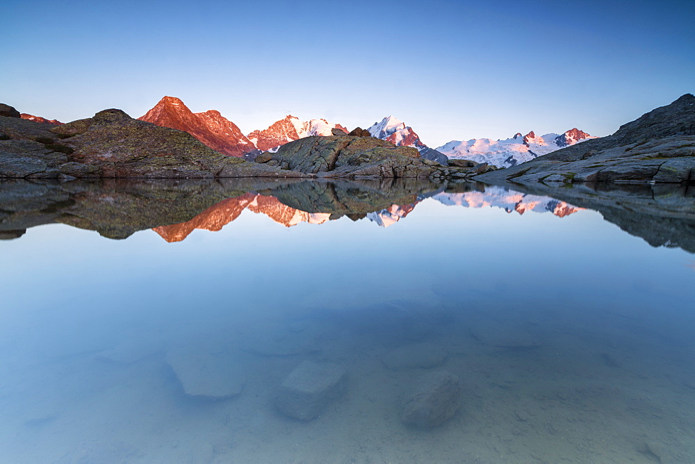 Snowy peaks reflected in the alpine lake at sunset, Fuorcla, Surlej, St. Moritz, Canton of Graubunden, Engadine, Switzerland, Europe - 1179-1471