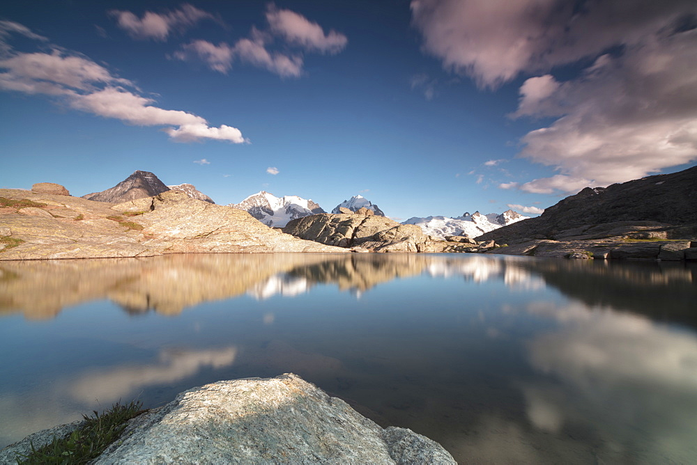 Pink clouds and peaks reflected in water at sunset, Fuorcla, Surlej, St. Moritz, Canton of Graubunden, Engadine, Switzerland, Europe