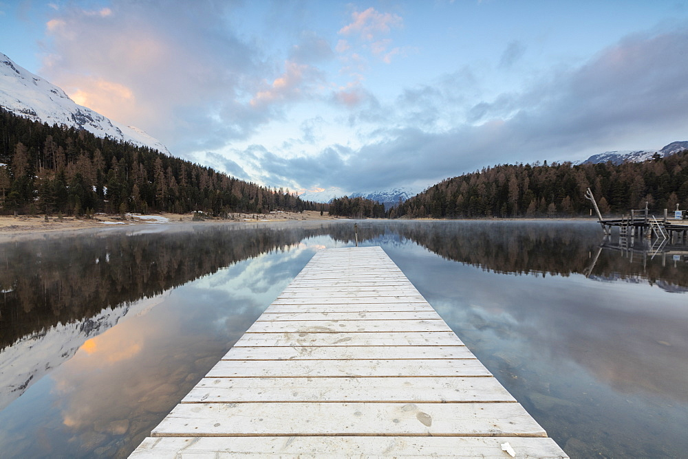 The wooden deck frames Lej Da Staz at dawn, St. Moritz, Canton of Graubunden, Engadine, Switzerland, Europe