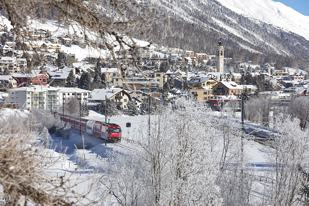 The red train runs across the snowy landscape around Samedan, Maloja, Canton of Graubunden, Engadine, Switzerland, Europe