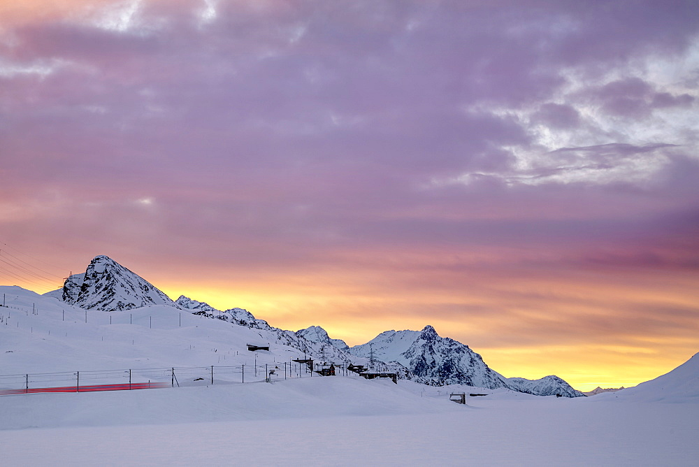 Pink clouds and snow frame the Bernina Express train at dawn, Bernina Pass, Canton of Graubunden, Engadine, Switzerland, Europe