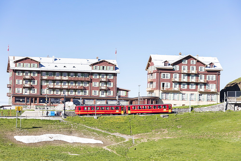 Red wagons of Wengernalpbahn rack railway run next to alpine hotels, Wengen, Bernese Oberland, Canton of Bern, Switzerland, Europe