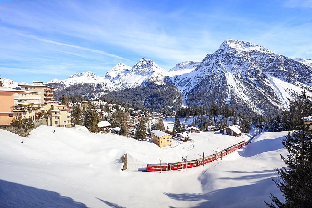 Red train of Rhaetian Railway passes in the snowy landscape of Arosa, district of Plessur, Canton of Graubunden, Swiss Alps, Switzerland, Europe