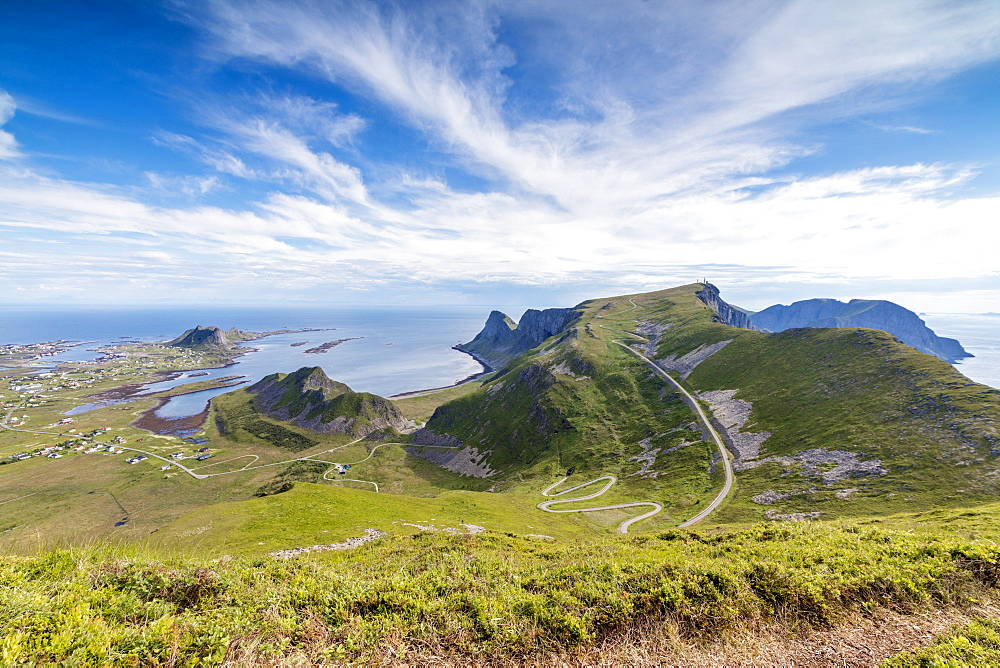 Steep road of curves in between green meadows and sea, Sorland, Vaeroy Island, county of Nordland, Lofoten Islands, Norway, Scandinavia, Europe