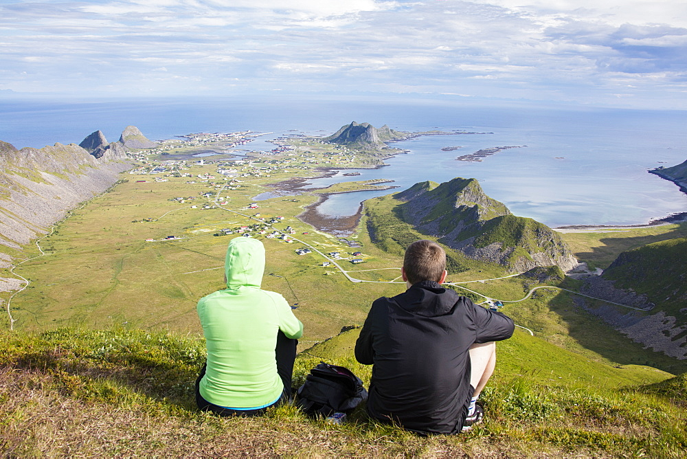 Couple on top of peak admire sea framing the village of Sorland, Vaeroy Island, Nordland county, Lofoten archipelago, Norway, Scandinavia, Europe