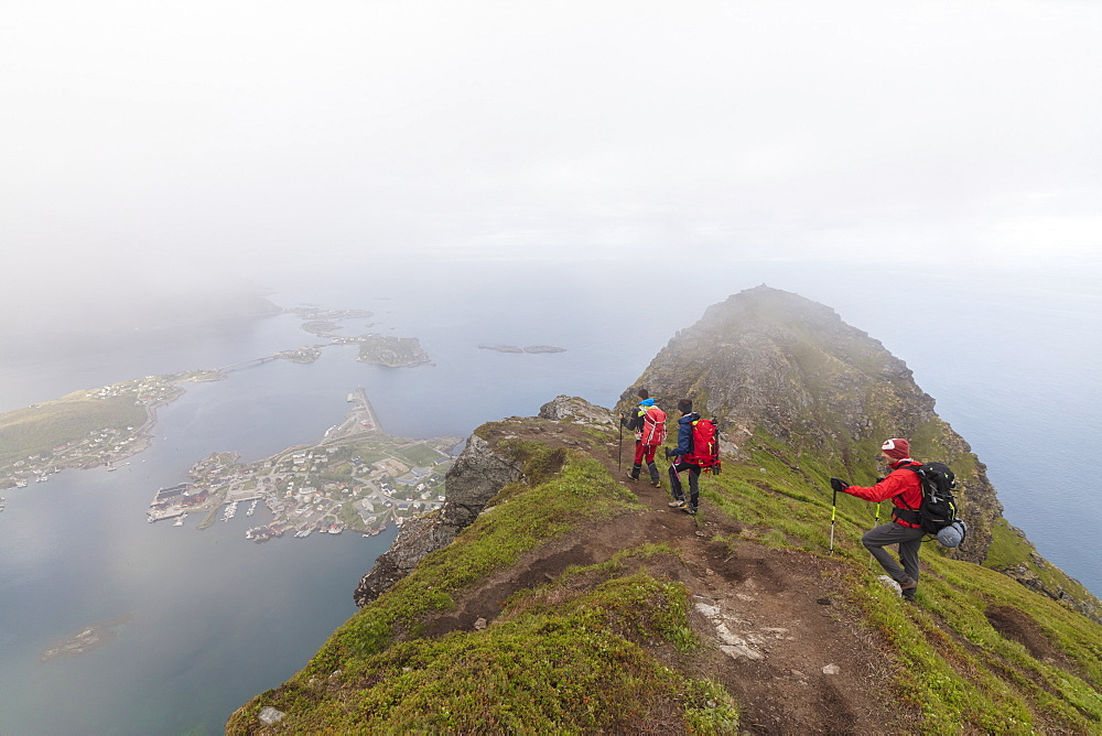 Hikers on top of rocky peak admire the blue sea surrounded by mist, Reinebringen, Moskenesoya, Lofoten Islands, Norway, Scandinavia, Europe