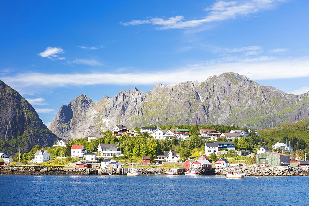 The blue sea frames the fishing village and the rocky peaks, Reine, Moskenesoya, Lofoten Islands, Norway, Scandinavia, Europe