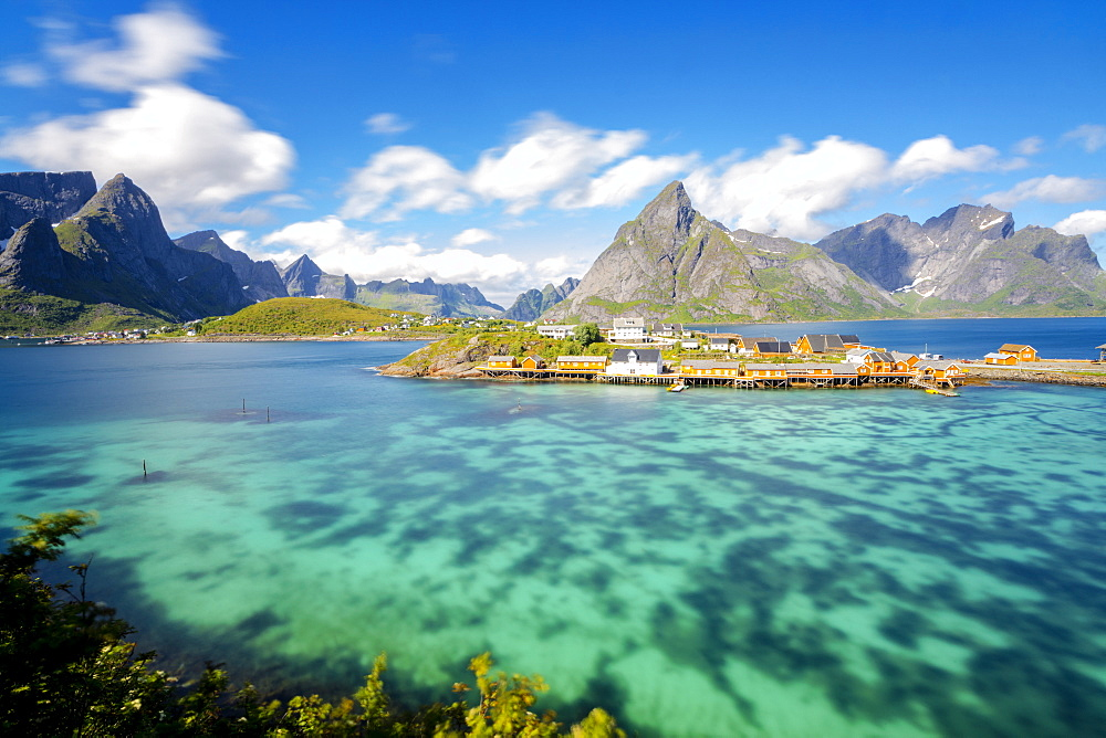 The turquoise sea frames the typical fishing village surrounded by rocky peaks, Sakrisoy, Reine, Moskenesoya, Lofoten Islands, Norway, Scandinavia, Europe
