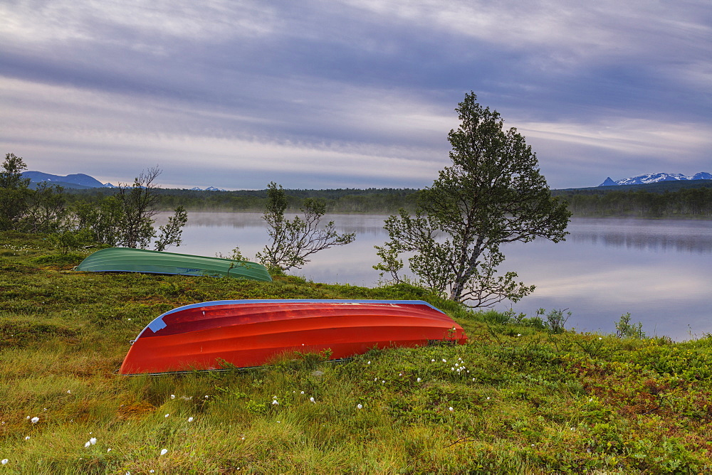 Boats on green meadows frame the calm water at night Bogen Evenes Ofotfjorden Norway Europe