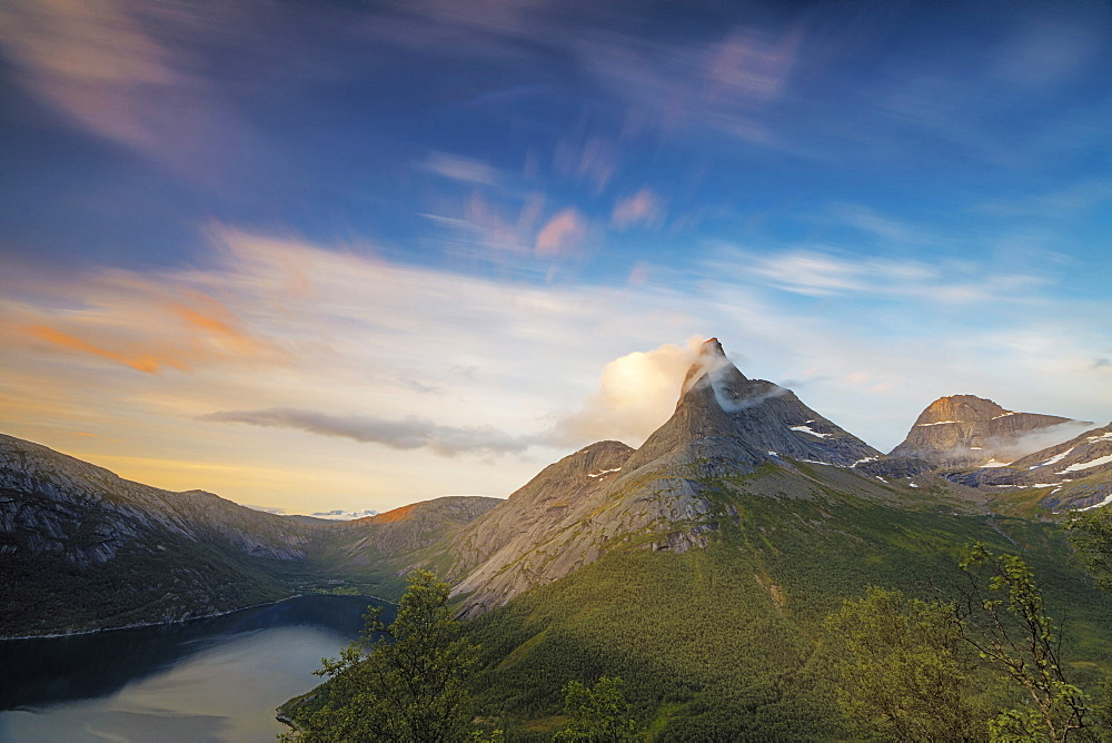 Pink sky and midnight sun light up the rocky peak of the Stetinden mountain surrounded by sea, Tysfjord, Nordland, Norway, Scandinavia, Europe
