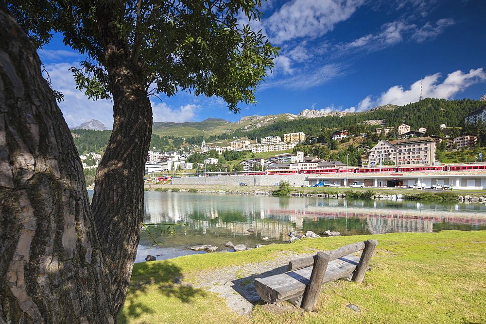 Bernina Express train runs across the village of St.Moritz surrounded by lake Canton of Graubünden Engadine Switzerland Europe