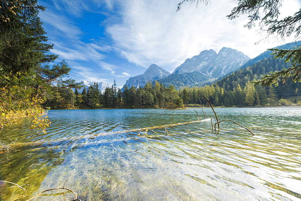 Lake Weissensee surrounded by woods with the Alps in the background Biberwier Carinthia Tyrol Austria Europe