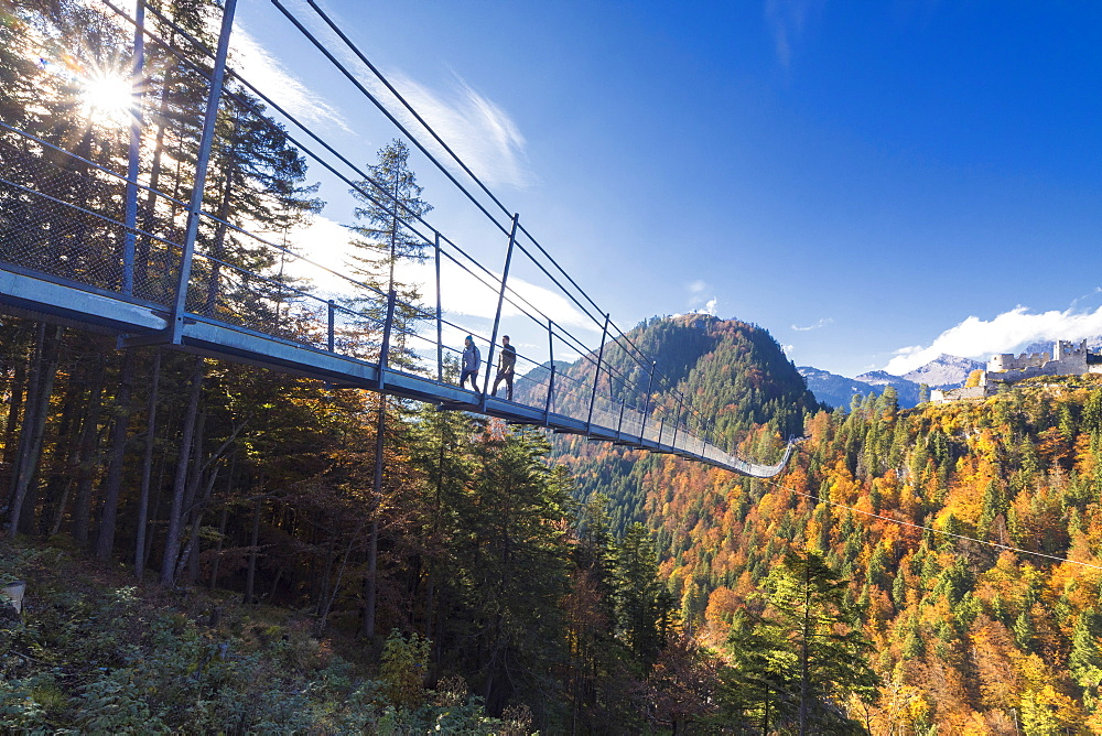 Tourists on the suspension bridge called Highline 179 framed by colorful woods in autumn Ehrenberg Castle Reutte Austria Europe