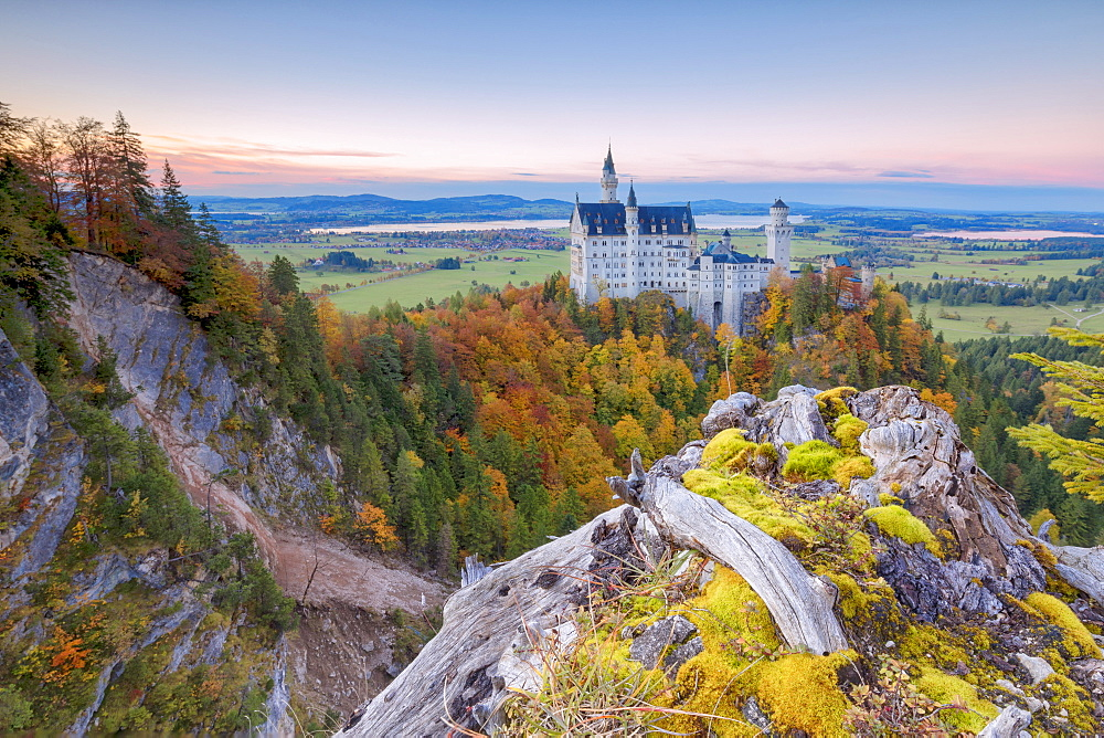 Sunset on Neuschwanstein Castle surrounded by colorful woods in autumn Füssen Bavaria Germany Europe
