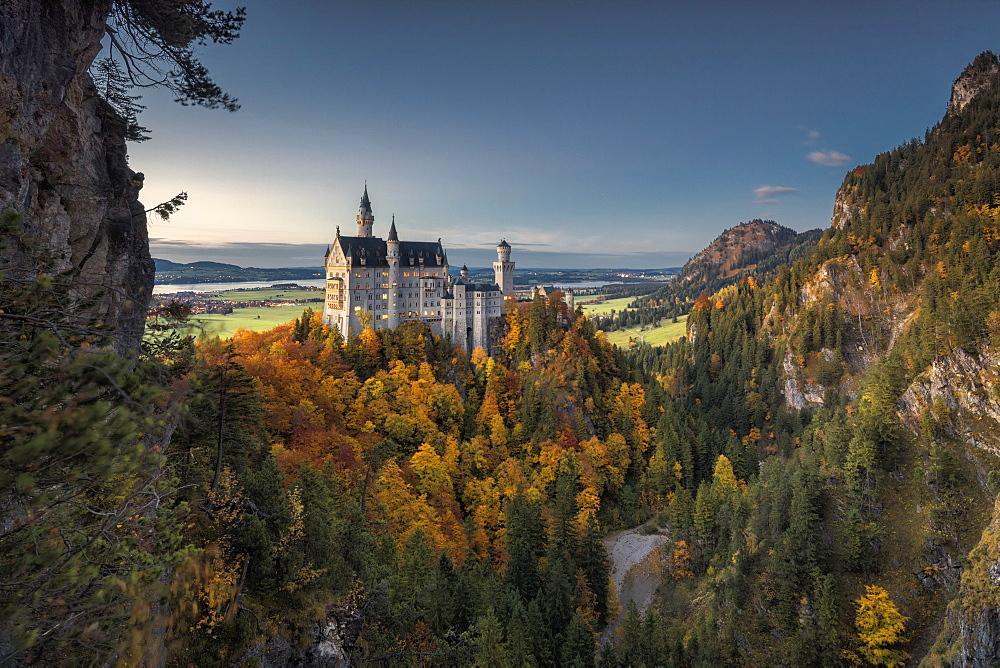 Dusk lights on Neuschwanstein Castle surrounded by colorful woods in autumn Füssen Bavaria Germany Europe