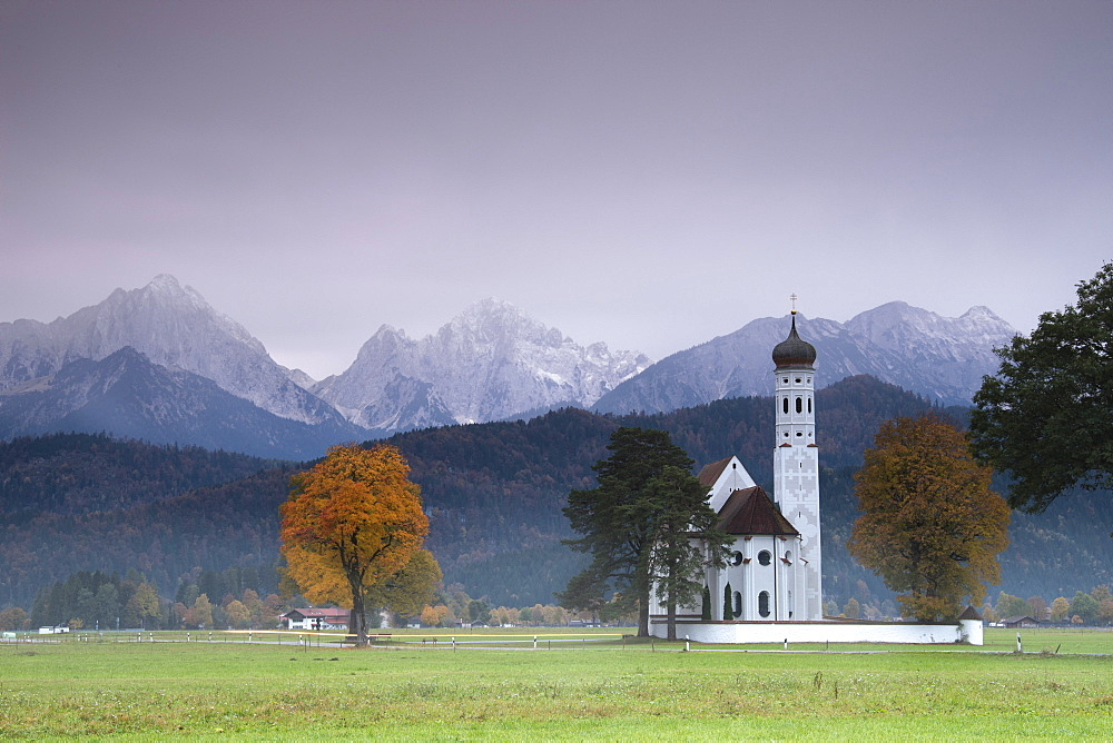 Pink sunrise on St Coloman Church surrounded by woods and mist of autumn Schwangau Bavaria Germany Europe