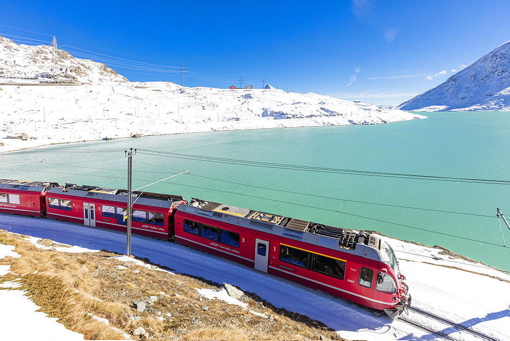 Bernina Express train in the snowy valley surrounded by Lake Bianco, Bernina Pass, Canton of Graubunden, Engadine, Switzerland, Europe