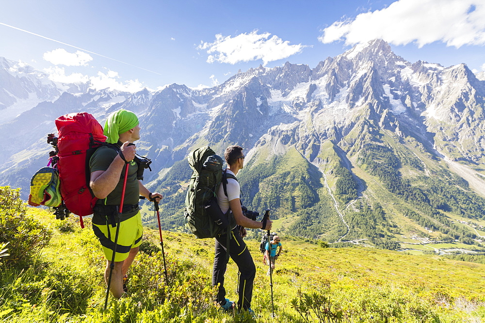 Hikers on steep path admire the rocky peaks of Mont De La Saxe Courmayeur Aosta Valley Italy Europe
