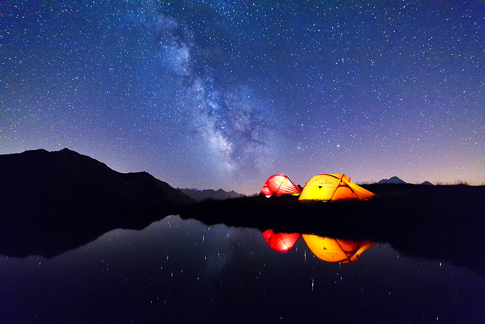 Tents reflected in the alpine lake on a starry night, Mont De La Saxe, Courmayeur, Aosta Valley, Italy, Europe