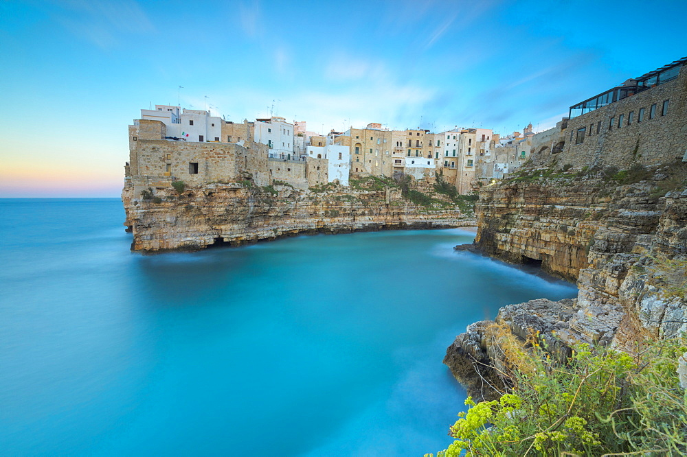 Turquoise sea at sunset framed by the old town perched on the rocks Polignano a Mare province of Bari Apulia Italy Europe