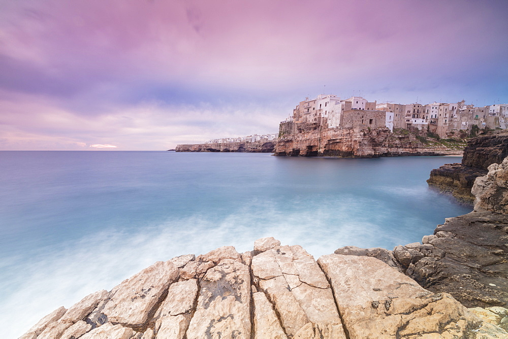 Pink sunrise on the turquoise sea framed by old town perched on the rocks, Polignano a Mare, Province of Bari, Apulia, Italy, Europe