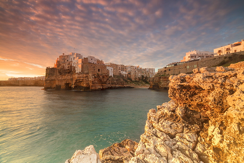 Pink sunrise on the turquoise sea framed by old town perched on the rocks Polignano a Mare province of Bari Apulia Italy Europe