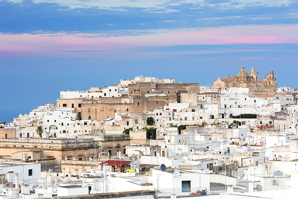 View of typical architecture and white houses of the old medieval town at sunset Ostuni province of Brindisi Apulia Italy Europe