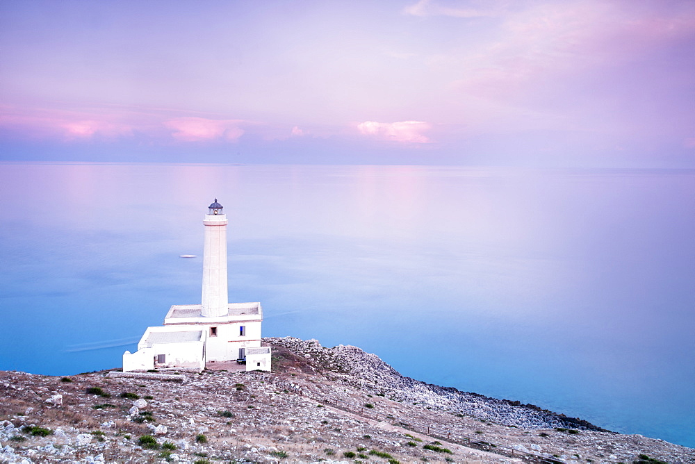 Pink sky on turquoise sea frames the lighthouse at Punta Palascia at sunset Otranto province of Lecce Apulia Italy Europe