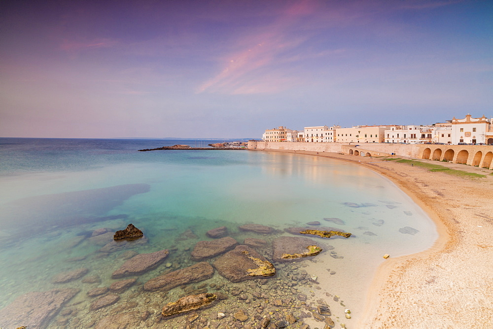 Turquoise sea frames the beach and the medieval old town at sunset Gallipoli province of Lecce Apulia Italy Europe