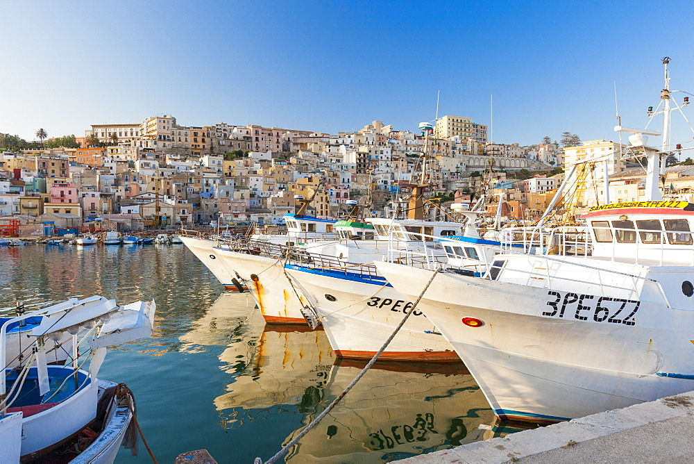 Fishing boats moored in the harbour surrounded by blue sea and the old town Sciacca province of Agrigento Sicily Italy Europe