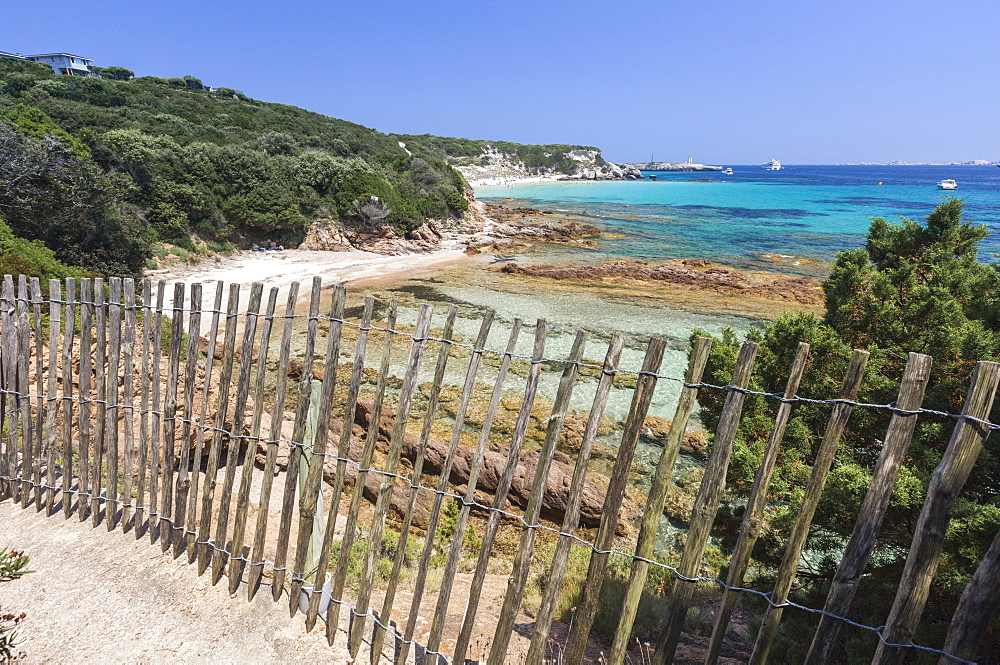 The wooden fence frames the limestone rocks and turquoise sea, Sperone, Bonifacio, South Corsica, France, Mediterranean, Europe