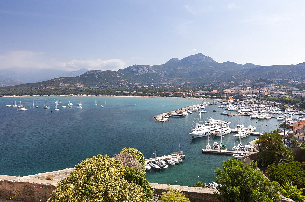 View of the harbor in the bay surrounded by the turquoise sea, Calvi, Balagne Region, northwest Corsica, France, Mediterranean, Europe