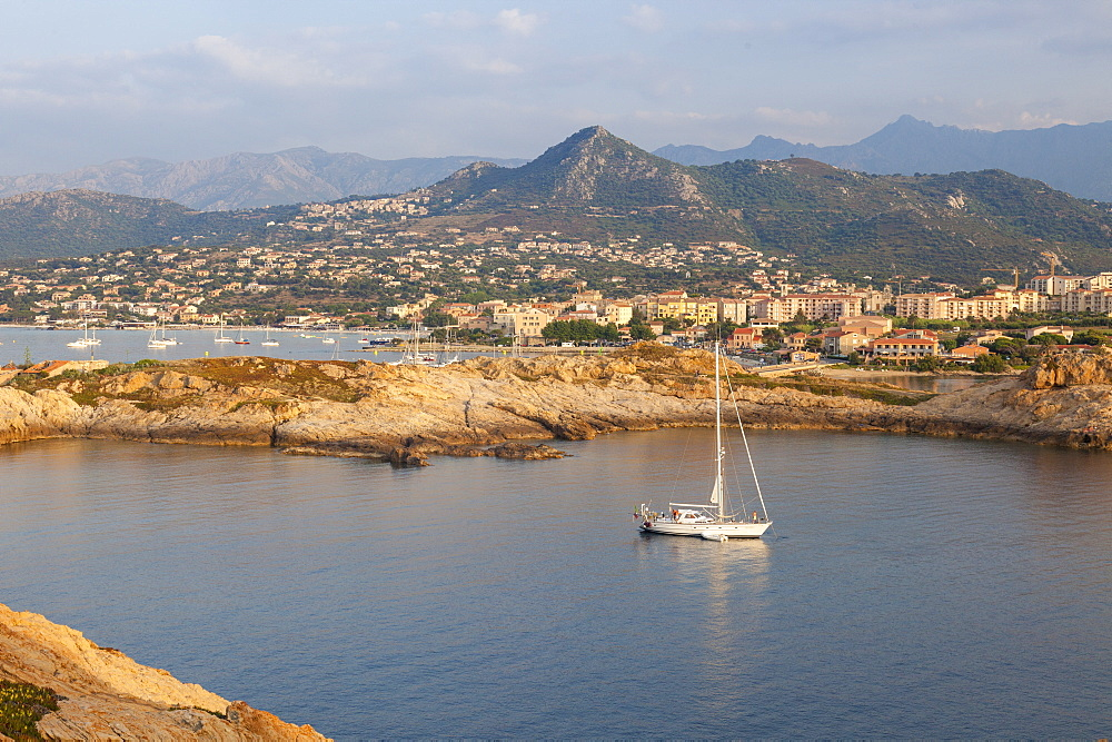 A sail boat in the clear sea around the village of Ile Rousse at sunset, Balagne Region, Corsica, France, Mediterranean, Europe