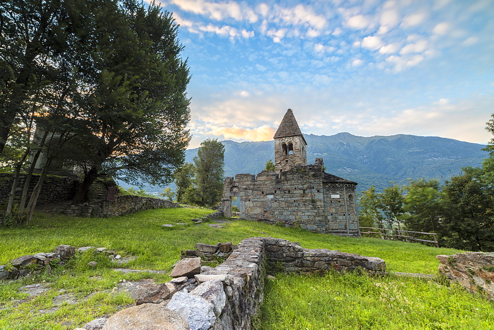 Green meadows frame the Abbey of San Pietro in Vallate at sunset, Piagno, Sondrio province, Lower Valtellina, Lombardy, Italy, Europe