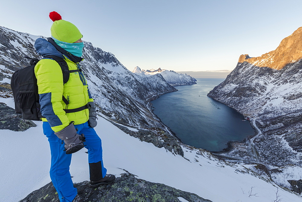 Hiker on top of the crest admires the village of Fjordgard framed by the frozen sea of the Ornfjorden Senja Tromsø Norway Europe