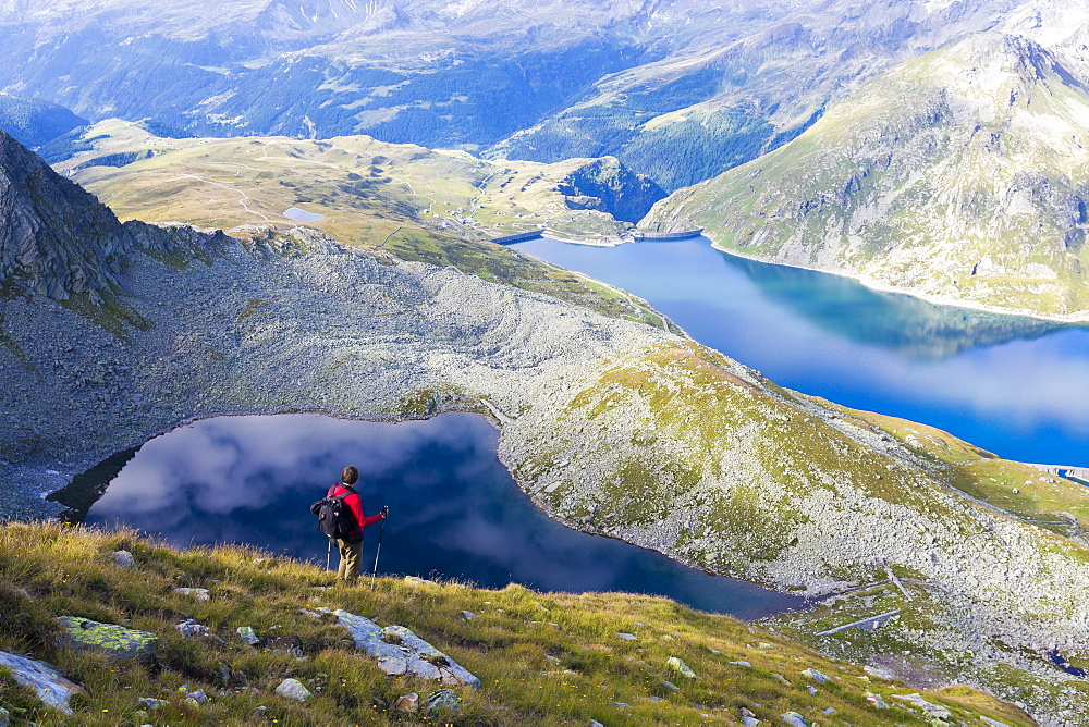 Hiker on the shore of Lago Nero admires the blue Lake Montespluga in summer, Chiavenna Valley, Valtellina, Lombardy, Italy, Europe