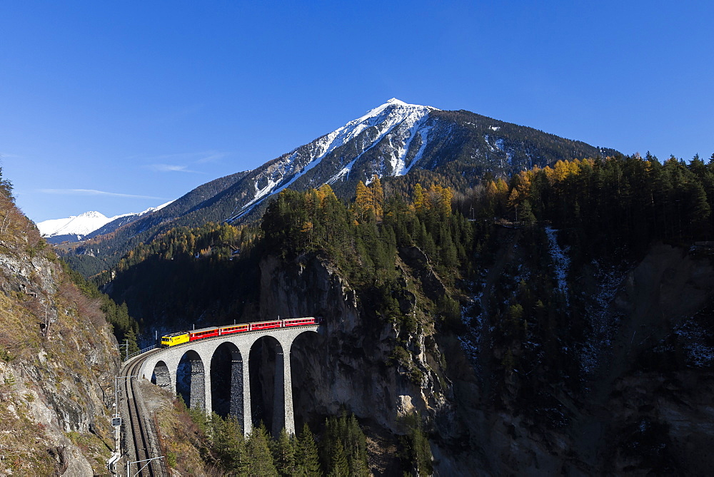 Bernina Express passes over Landwasser Viadukt surrounded by colorful woods, Canton of Graubunden, Switzerland, Europe
