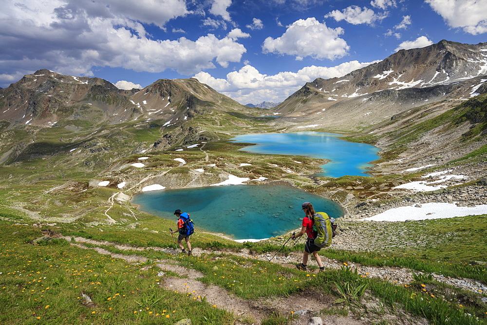 Hikers pass the turquoise lake and rocky peaks, Joriseen, Jorifless Pass, canton of Graubunden, Engadine, Switzerland, Europe