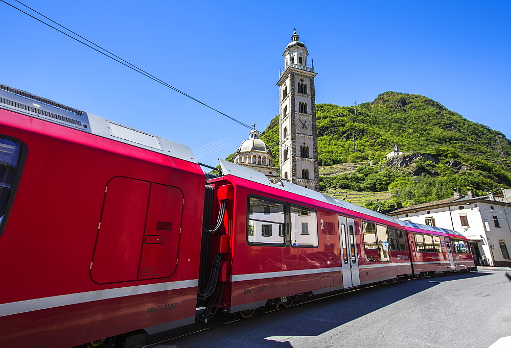 The Bernina Express train passes near the Sanctuary of Madonna di Tirano, not far from the Swiss border, on the UNESCO World Heritage Site railway, Lombardy, Italy, Europe