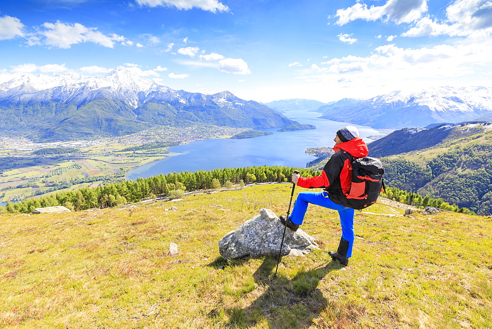 Hiker on green meadows admires Lake Como framed by snowy peaks Montemezzo Alpe Zocca Lombardy Italy Europe - 1179-2301