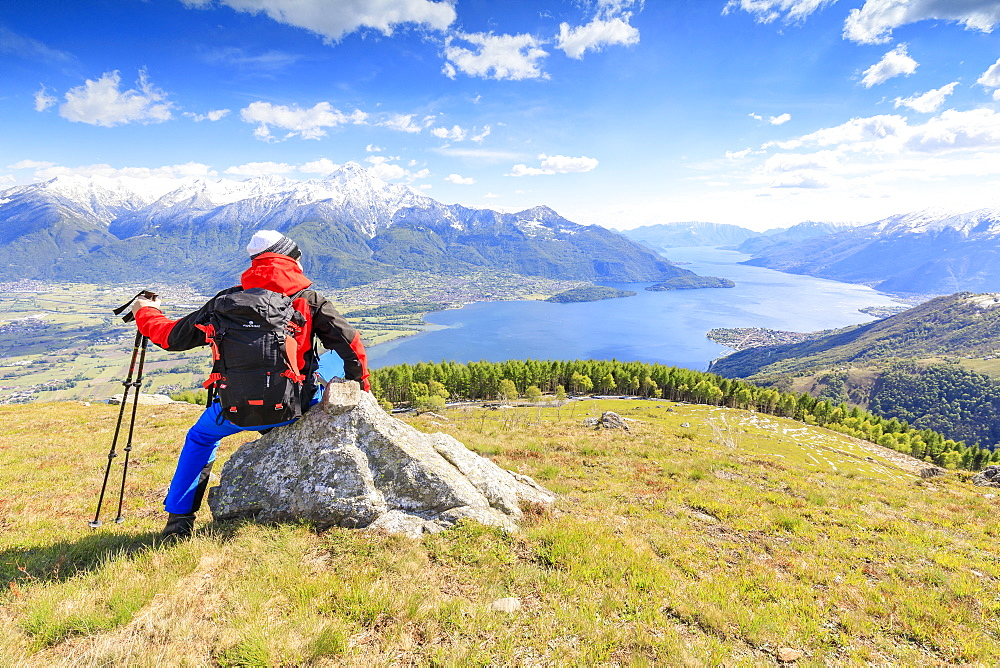 Hiker on green meadows admires Lake Como framed by snowy peaks Montemezzo Alpe Zocca Lombardy Italy Europe