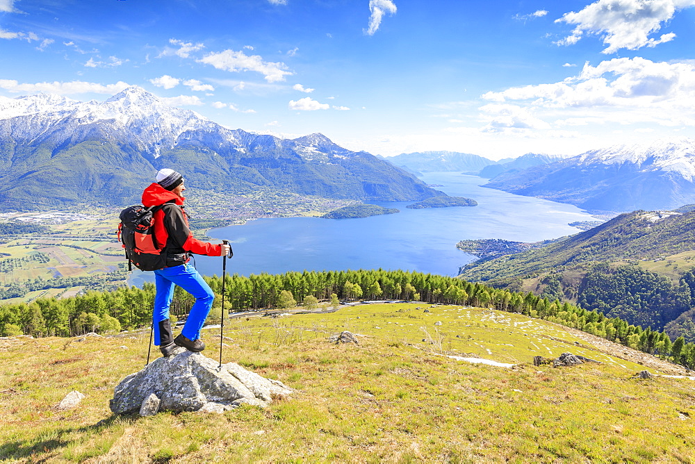 Hiker on green meadows admires Lake Como surrounded by woods Montemezzo Alpe Zocca Lombardy Italy Europe - 1179-2303
