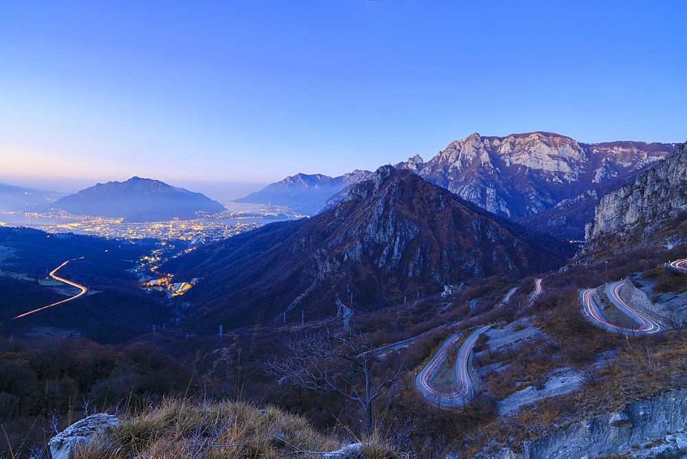 Dusk on the illuminated city of Lecco seen from the road to Morterone, Lombardy, Italy, Europe