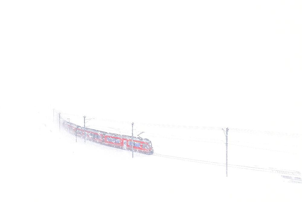 Bernina Express train at Bernina Pass during a snowstorm, Engadine, Canton of Graubunden, Switzerland, Europe