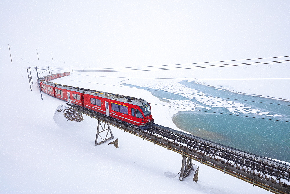 Bernina Express train at Bernina Pass under a snowfall, Engadine, Canton of Graubunden, Switzerland, Europe